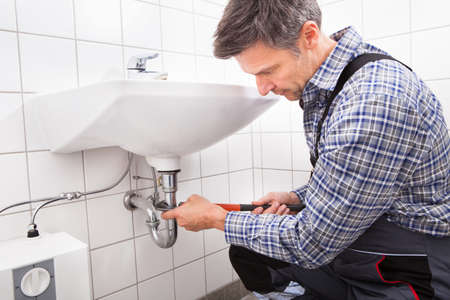 Mature Male Plumber Fitting Sink Pipe In Bathroom photo