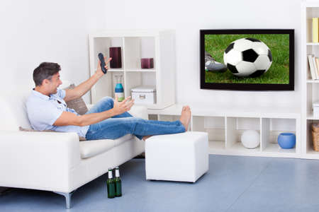 Portrait Of An Excited Mature Man Watching Soccer Game On Television photo
