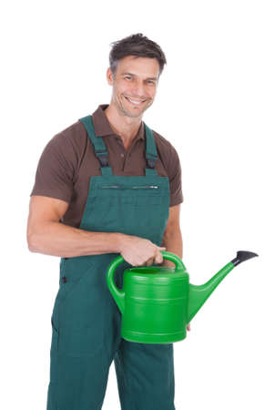 Portrait Of  Happy Mature Male Gardener Holding Watering Can photo