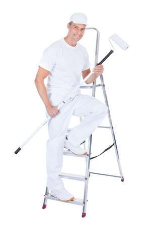Mature Male Painter With Paint Roller And Ladder Over White Background photo