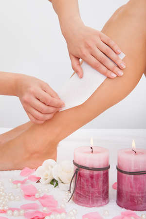 Beautician Waxing A Woman's Leg Applying Wax Strip Stock Photo - 24996291