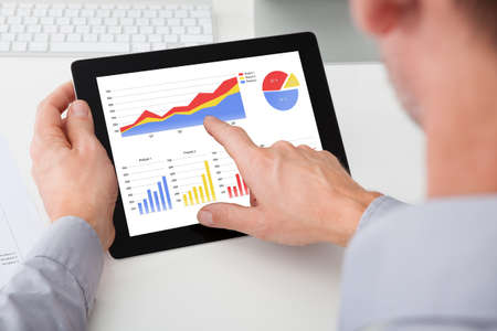 Close-up Of Businessman Analyzing Graph On Digital Tablet photo