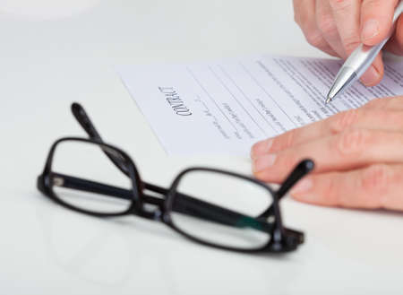 Close-up Of A Businessman Reading Contract Paper photo