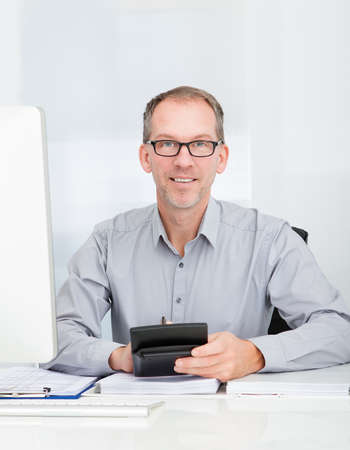 Happy Businessman Sitting In Front Of Computer Holding Calculator photo