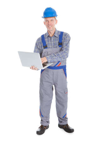 Portrait Of A Male Happy Architect Using Laptop On White Background photo