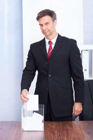 Happy Mature Businessman Inserting Ballot In Transparent Box photo