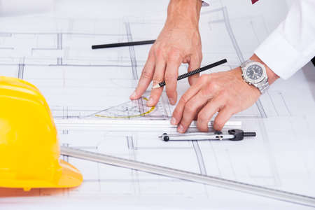 Close-up Of Male Architect Drawing Blueprint In Office photo