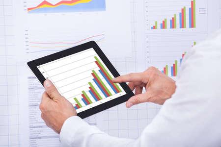 Mature Businessman Analyzing Graph On Digital Tablet photo