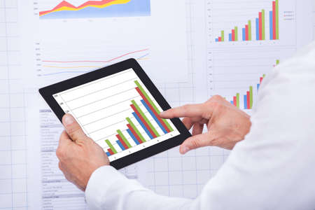 Mature Businessman Analyzing Graph On Digital Tablet Stock Photo