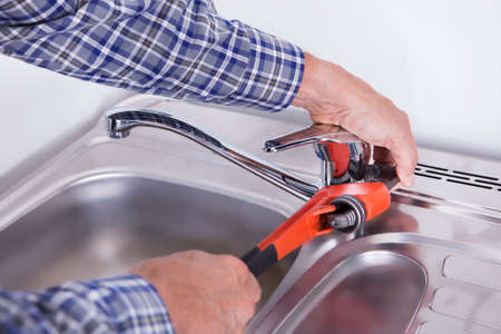 Close-up Of A Plumber Fixing Washbasin With Wrench photo