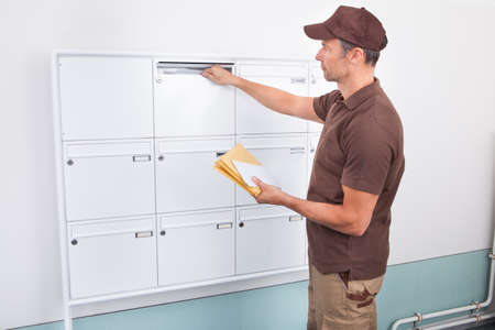 Portrait Of Mature Postman Putting Letters In Mailbox photo