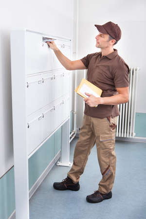 Portrait Of Mature Postman Putting Letters In Mailbox