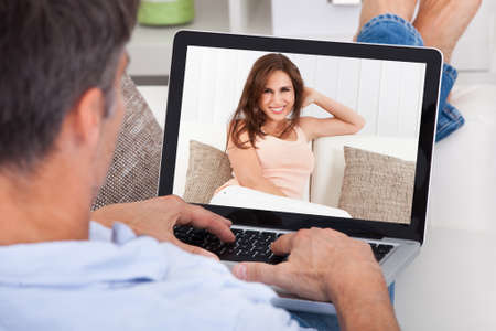 adult dating: Close-up Of A Man Chatting With Woman Using Laptop Stock Photo