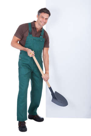 Portrait Of Cheerful Male Gardener With Shovel Presenting Blank Placard photo
