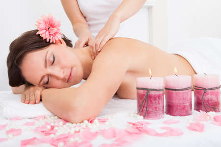 Smiling Young Woman Getting Massage Treatment From Masseuse Stock Photo - 25045413