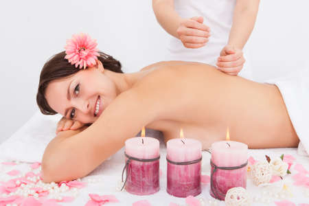 Smiling Young Woman Getting Massage Treatment From Masseuse Stock Photo - 25045414