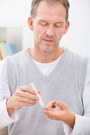 own blood: Mature Man Examining Blood Sugar Level Of His Own