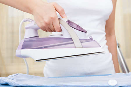 Close-up Of Woman's Hand Ironing Clothes On Ironing Board Stock Photo - 25045429