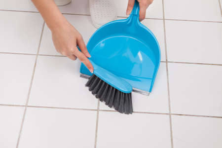 Close-up Of Woman Cleaning Floor With Broom And Dust Pan photo