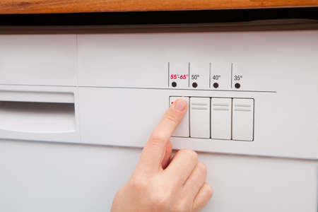 dish washing: Close-up Of Womans Finger Pressing Button Of Dishwasher