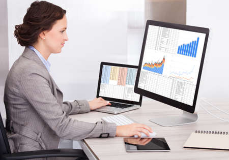 Portrait Of Young Businesswoman Analyzing Graph On Computer photo