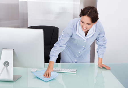 オフィスでクリーニング女性の幸せの用務員の肖像画 写真素材