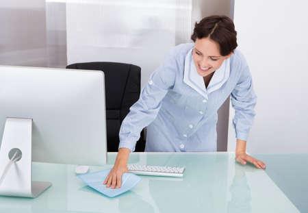 Portrait der glücklichen Frau Hausmeister Reinigung Schreibtisch im Büro Standard-Bild - 25045451