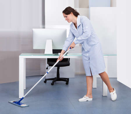 Portrait Of Happy Female Janitor Cleaning Floor At Office photo