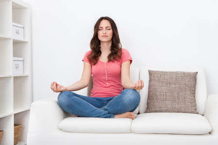 Portrait Of A Young Woman Sitting On Couch Practicing Yoga photo