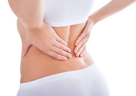 dolor muscular: Mujer joven con dolor en la espalda Sobre Fondo Blanco