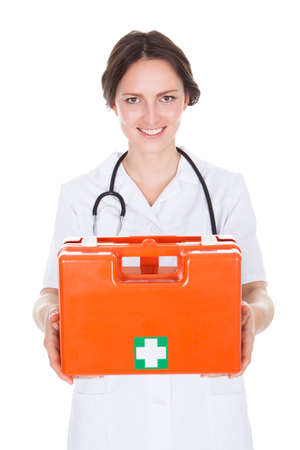 first aid box: Portrait Of Happy Female Doctor Holding First Aid Box Over White Background