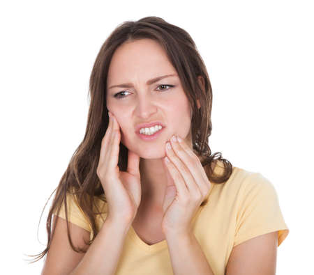 Close-up Of A Young Woman Suffering From Toothache Over White Background photo