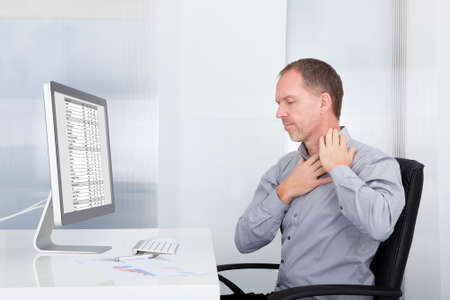senior man on a neck pain: Mature Businessman Using Computer Suffering From Neck Ache Stock Photo