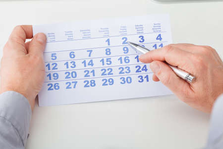 Close-up Of Man Marking With Pen And Looking At Date On Calendar photo
