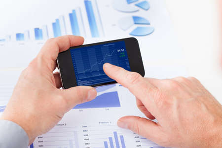 Close-up Of Businessman Analyzing Graph On Cell Phone photo