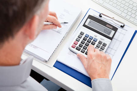 account executives: Close-up Of A Businessman Calculating Finance At Desk Stock Photo