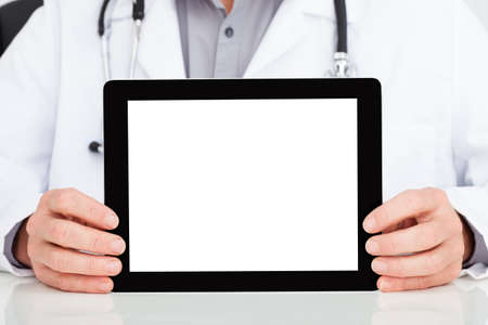 Close-up Of Mature Doctor Showing Blank Digital Tablet In Clinic photo