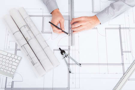 construction draftsman: Close-up Of Persons Hand Drawing Plan On Blue Print