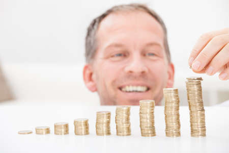 stacking: Portrait Of Happy Mature Man Sitting At Home Stacking Coins