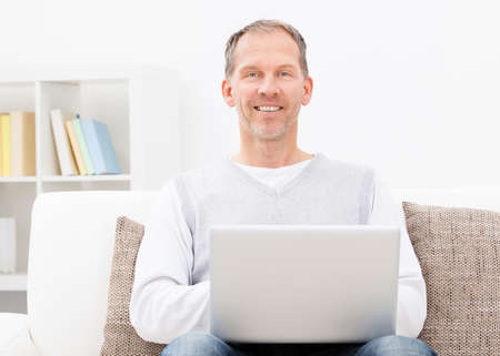 Happy Mature Man Sitting On Couch Using Laptop Stock Photo - 25045562