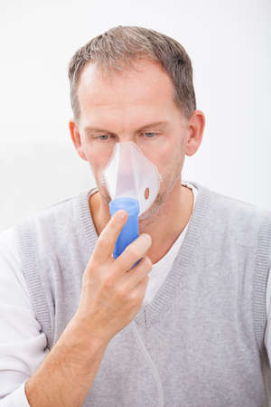 cystic: Man Doing Inhalation Through Oxygen Mask At Home Stock Photo