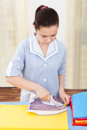 iron curtain: Portrait Of A Young Woman Ironing On Ironing Board