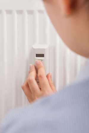 adjusting: Photo Of A Woman Adjusting Temperature With Digital Thermostat Stock Photo