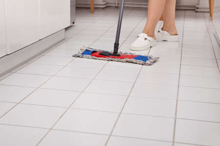 Close-up Van Jonge Maid In Uniform Cleaning Kitchen Floor