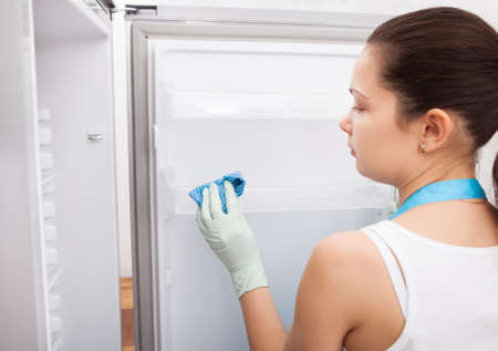 Rear View Of A Young Woman Cleaning Refrigerator photo