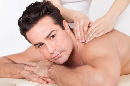 Shirtless Man Lying On Front Getting Spa Treatment Stock Photo
