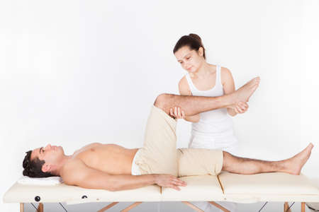 rehabilitation: Young Man Lying On Table Getting Foot Massage From Masseuse