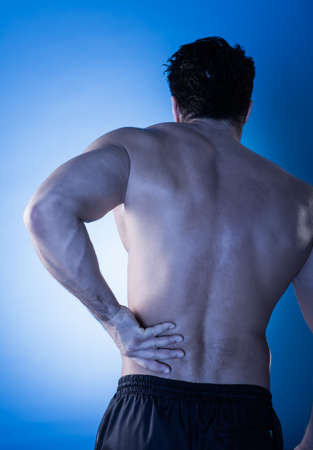 pain: Rear View Of Young Man Suffering From Back Pain Stock Photo
