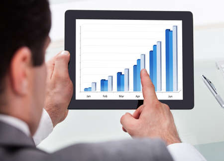 finance manager: Close-up Of A Businessman Analyzing Graph On Digital Tablet Stock Photo