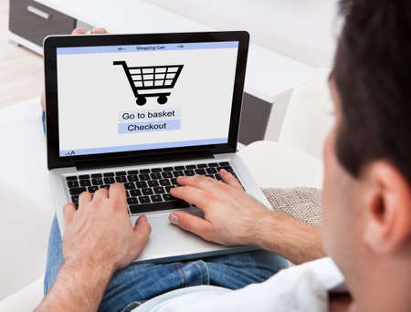 shopping online: Businessman Using Laptop With Online Shopping Application On A Screen